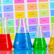 Laboratory flasks with color liquid on color samples background - Foto de Stock