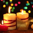 Beautiful candles on wooden table on bright background - Stock Photo