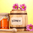 Sweet honey in barrel and jar with drizzler on wooden table on yellow background - Zdjęcie stockowe