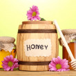 Sweet honey in barrel and jars with drizzler on wooden table on green background - Foto de Stock