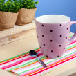 Coffee cup on table in cafe on blue background - Stock Photo