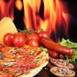 Delicious pizza, salami, tomatoes and spices on wooden table on flame background - Stock Photo