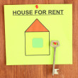 Poster about renting the house with the key on wooden background - Photo