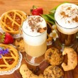 Glasses of coffee cocktail on wooden table with sweet and flowers — Stock Photo