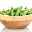 Green peas in wooden bowl isolated on white - Stock Photo