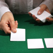 Cards in hands on green table - Stock Photo