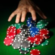 Poker chips and hand above it on green table - Stock Photo