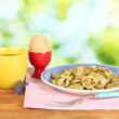 Stock Photo: Fried zucchini with eggs and coffee for breakfast on wooden table on green background