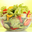 Fresh vegetable salad in transparent bowl on green background — 图库照片