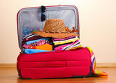 Open red suitcase with clothing in the room — Stockfoto