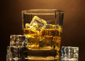 Glass of scotch whiskey and ice on brown background — Stock Photo