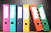 Bright office folders on wooden table on grey background — Stock Photo