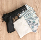 Cocaine in package, dollars and handgun on wooden background — Stock Photo