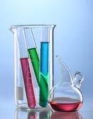Cristalería de laboratorio con líquido de color y con reflexión sobre fondo azul — Foto de Stock