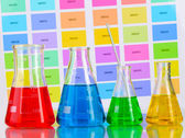 Frascos de laboratório com líquido de cor na cor de fundo de amostras — Foto Stock
