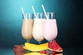 Melk schudt met vruchten en chocolade op blauwe achtergrond — Stockfoto