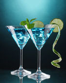 Blue cocktail in martini glasses on blue background — Stock Photo