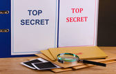 Envelopes and folders with top secret stamp and magnifying glass with photo papers on wooden table on brown background — Stock Photo