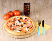 Aromatic pizza and cola on wooden background — Stock Photo