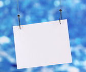 Empty sheet of a paper on fish hooks on blue background — Stock Photo