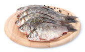 Fresh fishes with spice on wooden cutting board isolated on white — Stock Photo