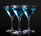 Blue cocktail in martini glasses isolated on black — Stock Photo