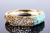 Beautiful golden bracelet on grey background — Стоковое фото