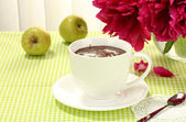 Cup hot chocolate, apples and flowers on table in cafe — Stock Photo