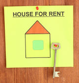 Poster about renting the house with the key on wooden background — Stock Photo