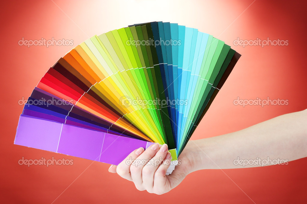 Hand holding bright palette of colors on red background — Stock Photo #10986782