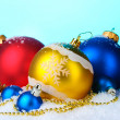 Beautiful bright Christmas balls and cones in snow on blue background — Stock Photo