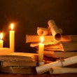 Pile of old books with candle and scroll in dark — Stock Photo #10992433