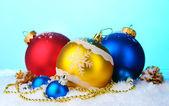 Krásné světlé vánoční koule a šišky ve sněhu na modrém pozadí — Stock fotografie