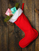 Christmas sock with gifts on wooden background — 图库照片