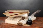 老书、 卷轴、 羽毛笔和灰色的背景上的木桌子上的墨水瓶 — 图库照片
