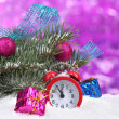 Green Christmas tree with toy and clock in the snow on purple — Stock Photo