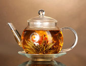 Glass teapot with exotic green tea on wooden table on brown background — Stock Photo