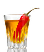 Bottle and glass of pepper vodka and red chili pepper isolated on white — Stock Photo