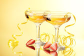 Glasses of champagne and strawberries on yellow background — Stock Photo