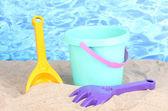 Zabawki dla dzieci plaży na piasku na tle wody — Zdjęcie stockowe