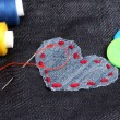Heart-shaped patch on jeans with threads and buttons closeup - Stock Photo