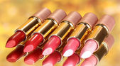 Beautiful lipsticks on yellow background — Stock Photo