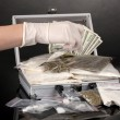 Cocaine and marijuana in a suitcase wiht hand holding a package of cocaine isolated on white — Stock Photo