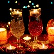 Foto Stock: Amazing composition of candles and glasses on wooden table on bright background