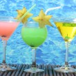 Stock Photo: Glasses of cocktails on table on blue sebackground