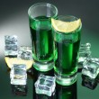 Two glasses of absinthe, lemon and ice on green background — Foto de Stock
