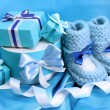 Beautiful gifts and baby's bootees on blue silk - Stock Photo