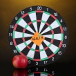 Darts with a sticker symbolizing health on colorful background - Stock Photo