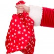 Santa Claus hand holding bag of gifts isolated on white - Stock Photo