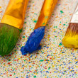 Brushes with colorful paint on colorful splashes background close-up — Stock Photo